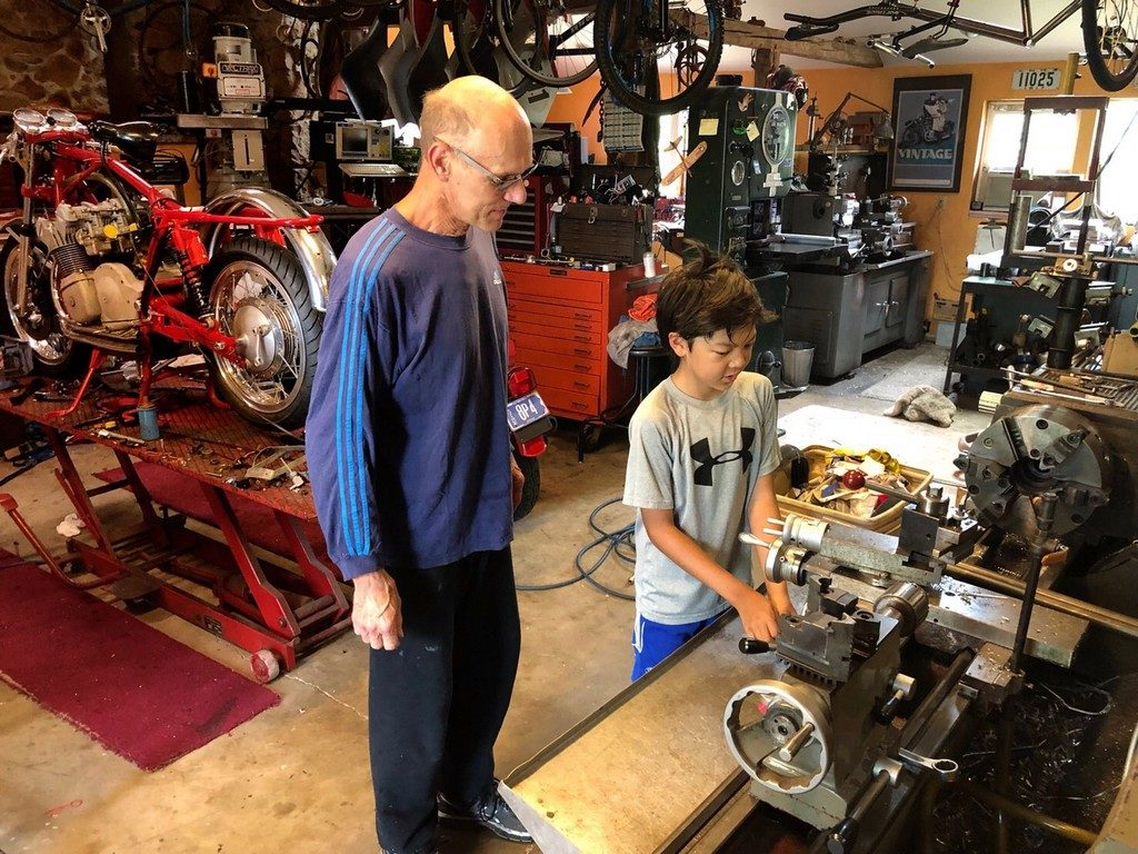 Albert patiently showing Jake how a lathe works.